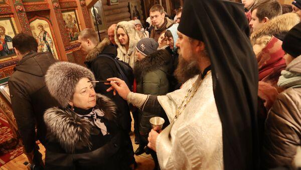 Верующие со священнослужителем во время традиционного праздничного молебна в Крещенский сочельник в Храме Святителя Николая в Измайловском Кремле в Москве - Sputnik Italia