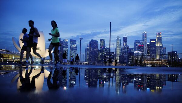 Joggers run past as the skyline of Singapore's financial district is seen in the background - Sputnik Italia