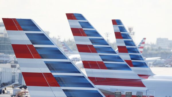 Painted vertical stabilizers are viewed as American Airlines jets are parked on the airport apron, Monday, Nov. 6, 2017, at Miami International Airport in Miami. American Airlines and a subsidiary will pay $9.8 million in stock to settle claims that they failed to help disabled employees return to work. - Sputnik Italia
