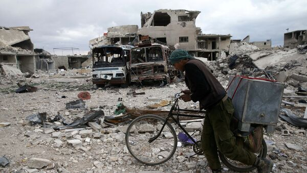 A man walks with his bicycle at a damaged site in the besieged town of Douma, Eastern Ghouta, in Damascus, Syria - Sputnik Italia