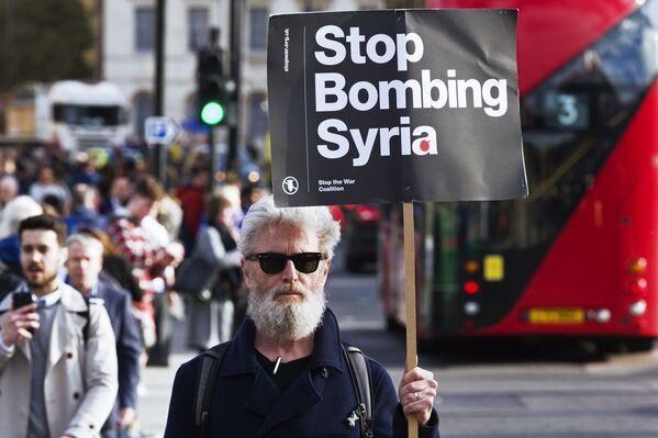 Un uomo tiene un cartello contro i bombardamenti in Siria alle proteste a Londra. - Sputnik Italia