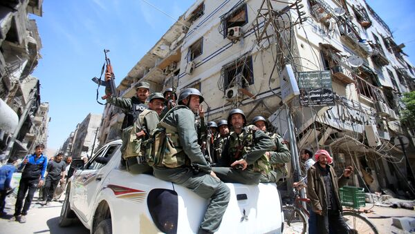 Members of the Syrian police hold their weapons as they sit on a back of a truck at the city of Douma, Damascus, Syria April 16, 2018 - Sputnik Italia
