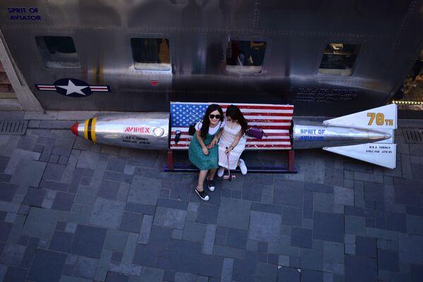 Ragazza si fanno fotografare su una panchina-missile in un negozio di Pechino. - Sputnik Italia