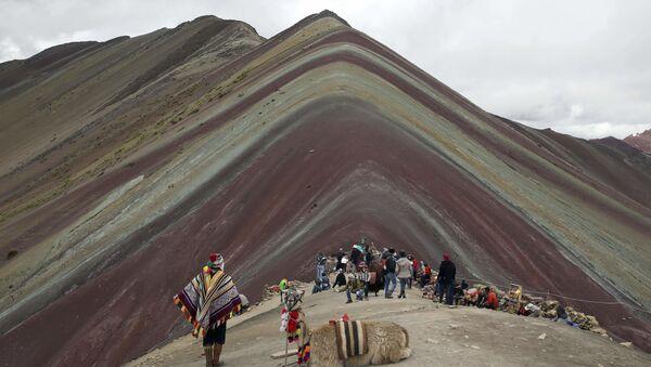 Un locale delle Ande con un lama e turisti stanno vicino alla Montagna Arcobaleno di Vinicunca in Perù. - Sputnik Italia