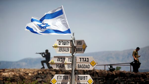 An Israeli soldier stands next to signs pointing out distances to different cities, on Mount Bental, an observation post in the Israeli-occupied Golan Heights that overlooks the Syrian side of the Quneitra crossing, Israel May 10, 2018 - Sputnik Italia