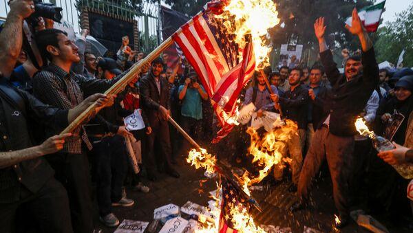 La bandiera statunitense viene bruciata durante le proteste a Teheran, Iran - Sputnik Italia