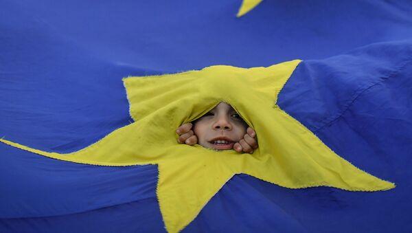 Un bambino guarda tra la bandiera dell'UE durante una manifestazione a Bucarest. - Sputnik Italia