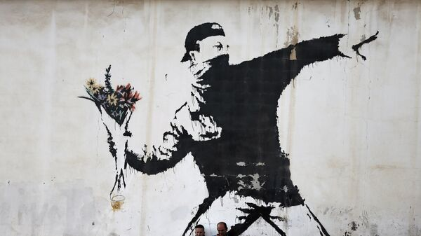 Two men are sitting in front of a famous graffiti of British street artist Banksy, painted on a wall of a gas station in the West Bank city of Bethlehem on December 16, 2015.  - Sputnik Italia