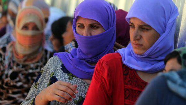 Yazidi Iraqi women queue in order to get food at the Bajid Kandala camp near the Tigris River, in Kurdistan's western Dohuk province, where they took refuge after fleeing advances by Islamic State jihadists in Iraq on August 13, 2014. (File) - Sputnik Italia