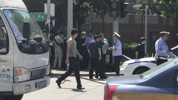 Officials and security personnel stand near the site of a reported blast outside the U.S. Embassy in Beijing, Thursday, July 26, 2018. - Sputnik Italia