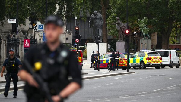 Armed police stand in the street after a car crashed outside the Houses of Parliament in Westminster, London, Britain, August 14, 2018 - Sputnik Italia
