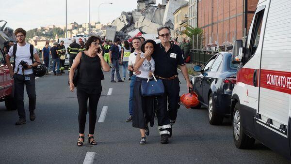 Un vigile di fuoco accompagna una donna al sito del crollo del ponte Morandi a Genova - Sputnik Italia