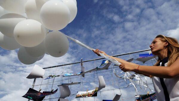 Una ragazza di Donetsk lancia in aria un palloncino bianco durante una manifestazione per la pace - Sputnik Italia