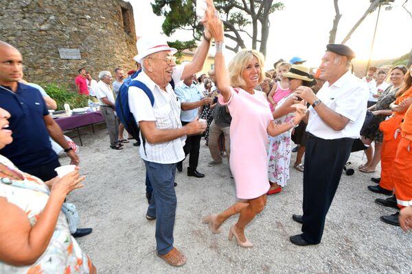 Brigitte Macron balla durante la festa per il 74 anniversario della liberazione della città di Bormes-les-Mimosas durante la Seconda guerra mondiale. - Sputnik Italia