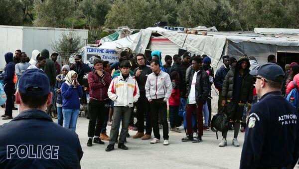 Poliziotti guardano migranti al campo per i rifugiati di Moria sull'isola di Lesbo, Grecia - Sputnik Italia