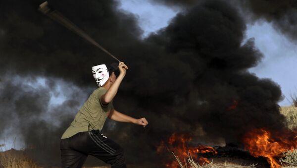 Un manifestante lancia un sasso all'esercito israeliano alla frontiera tra la striscia di Gaza ed Israele. - Sputnik Italia