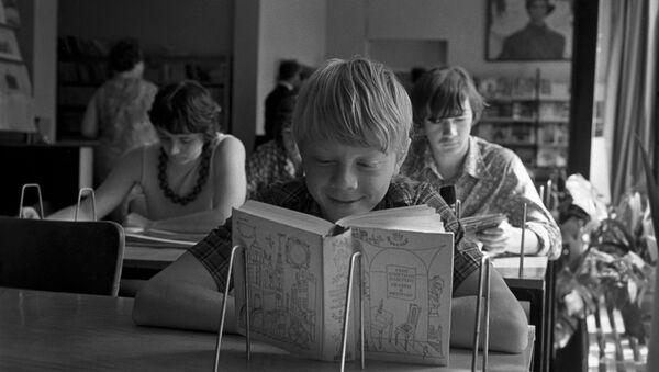 Un ragazzo legge un libro in biblioteca - Sputnik Italia