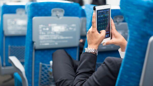 Бизнесмен с телефоном в руках в салоне самолета - Sputnik Italia