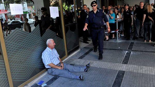 Un uomo, un pensionato greco, piange disperato seduto per terra fuori da una banca di Salonicco. - Sputnik Italia