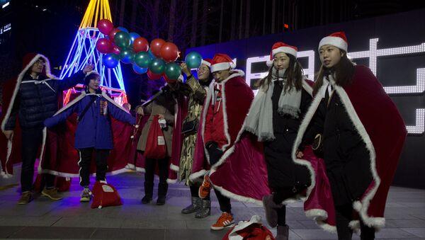 Giovani cinesi vestiti come gli aiutanti di Babbo Natale a Pechino, Cina. - Sputnik Italia