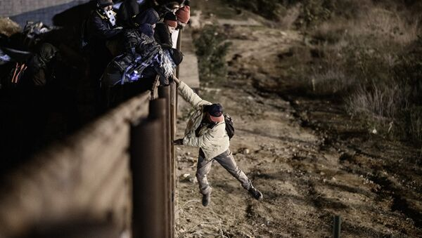 A migrant jumps the border fence to get into the U.S. side to San Diego, Calif., from Tijuana, Mexico, Tuesday, Jan. 1, 2019 - Sputnik Italia