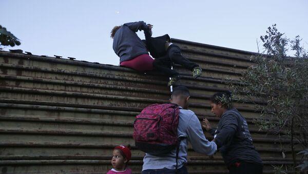 Honduran migrants help each other to cross over the U.S. border wall to San Diego, California, from Tijuana, Mexico, Saturday, Dec. 15, 2018 - Sputnik Italia