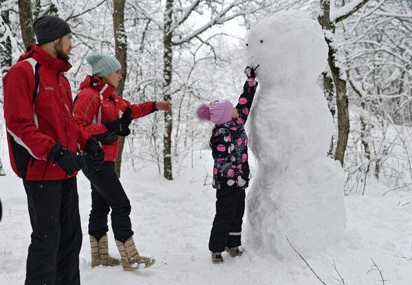 Una famiglia ed un pupazzo di neve al passo di Angarskij. - Sputnik Italia