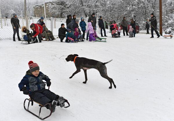 Un ragazzino sulla slitta al passo di Angarskij. - Sputnik Italia