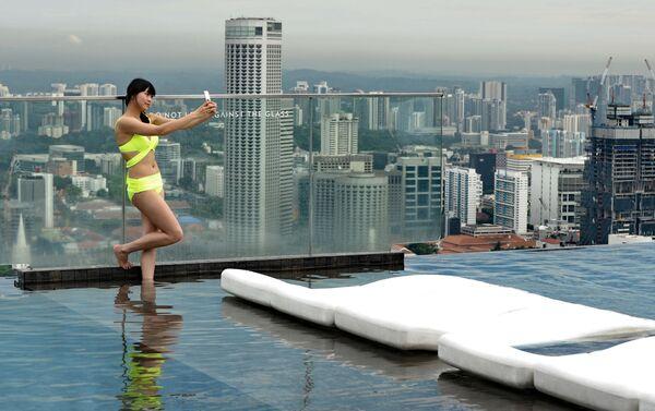Una turista si fa selfie alla terrazza dell'hotel Marina Bay Sands a Singapore. - Sputnik Italia