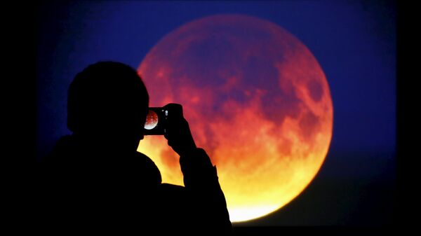 A man takes picture of the screen displaying the moon, appearing in a dim red colour, which is covered by the Earth's shadow during a total lunar eclipse in Warsaw, Poland September 28, 2015 - Sputnik Italia