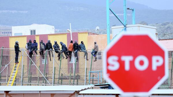 Would-be immigrants sit atop a border fence separating Morocco from the north African Spanish enclave of Melilla in the first attempt to jump in on February 19, 2015 - Sputnik Italia