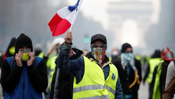 Masked protesters wearing yellow vests, a symbol of a French drivers' protest against higher fuel prices, take part in a demonstration on the Champs-Elysees in Paris, France, November 24, 2018 - Sputnik Italia