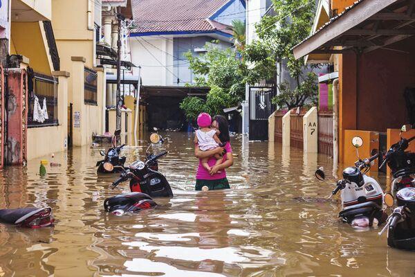 Una donna sta portando un bambino in una via inondata in una città indonesiana Makassar. - Sputnik Italia