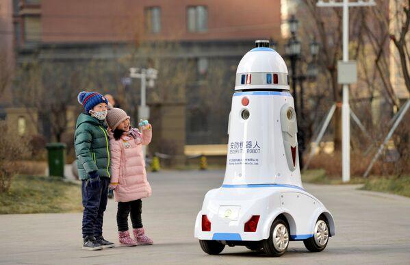 Bambini guardano un robot vigilante in una città cinese di Hohhot. - Sputnik Italia