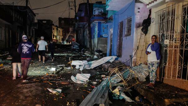 Cubans walk past debris in the tornado-hit Luyano neighbourhood in Havana early on January 28, 2019 - Sputnik Italia