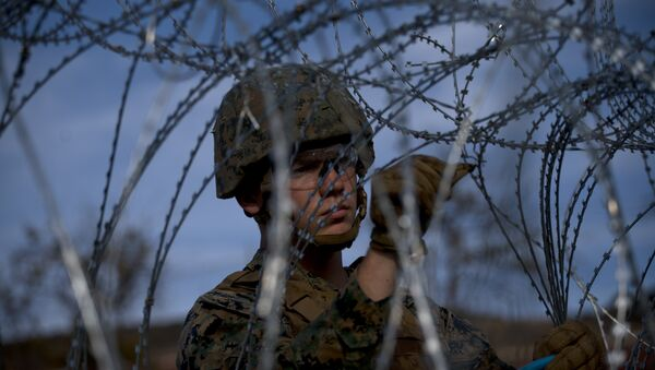 A soldier agent sets up barbed wire at the San Ysidro port of entry, at the U.S.-Mexico border, seen from Tijuana, Mexico, Thursday, Nov. 22, 2018 - Sputnik Italia