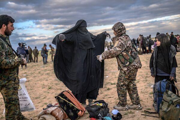 Membro delle Forze Siriane Democratiche fà prequisizione delle persone che hanno lasciato l'ultima basa del Daesh a Baghouz. - Sputnik Italia
