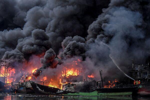 I vigili del fuoco estinguono il rogo nel porto di Muara Baru a Giacarta, Indonesia. - Sputnik Italia