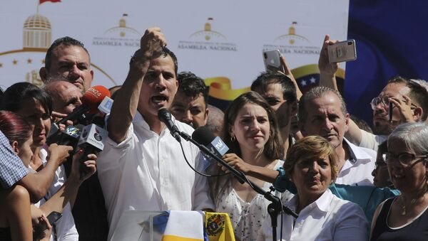 Juan Guaido, president of National Assembly, shows marks on his wrists, which he says are from handcuffs, to supporters at a rally in Caraballeda, Venezuela, Sunday, Jan. 13, 2019. The new head of Venezuela's increasingly defiant congress was pulled from his vehicle and briefly detained by police Sunday, a day after the U.S. backed him assuming the presidency as a way out of the country's deepening crisis. Guaido's wife Fabiana Rosales stands next to him, right. (AP Photo/Fernando Llano) - Sputnik Italia