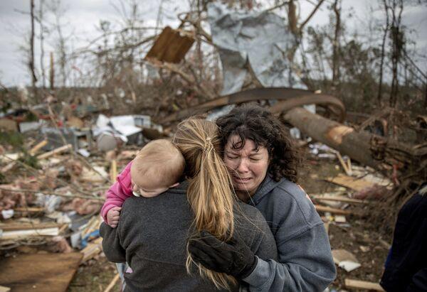 Una famiglia sta piangendo alle rovine della casa distrutta dal tornado, Beauregard, Alabama, USA. - Sputnik Italia
