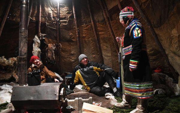 Una donna in costume tipico accoglie i visitatori nella sua tenda, villaggio etnico dell'Universiade 2019, sull'isola Tatyshev a Krasnoyarsk - Sputnik Italia