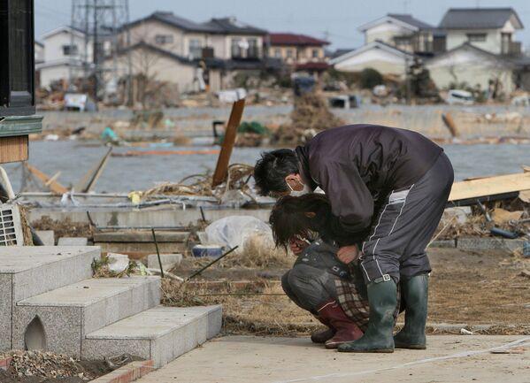 Un uomo cerca di confortare una donna in lacrime a Watari nella prefettura di Miyagi, 3 giorni dopo terremoto e tsunami - Sputnik Italia
