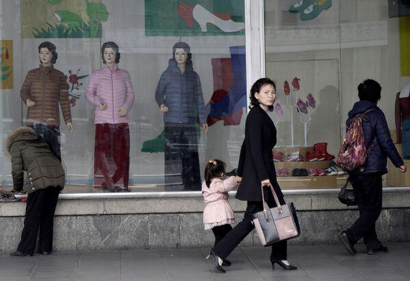 Una donna tiene per mano sua figlia a passeggio davanti ad una vetrina di un negozio d'abbigliamento a Pyongyang - Sputnik Italia