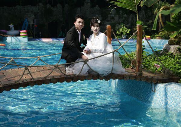 Una coppia di sposini posa per una foto del servizio di nozze in una piscina di Pyongyang - Sputnik Italia
