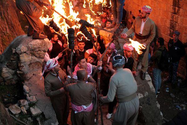 Curdi iracheni accendono delle torce: il fuoco, simbolo di calore, luce e rinascita è uno dei principali attributi della festa del Nowruz  - Sputnik Italia