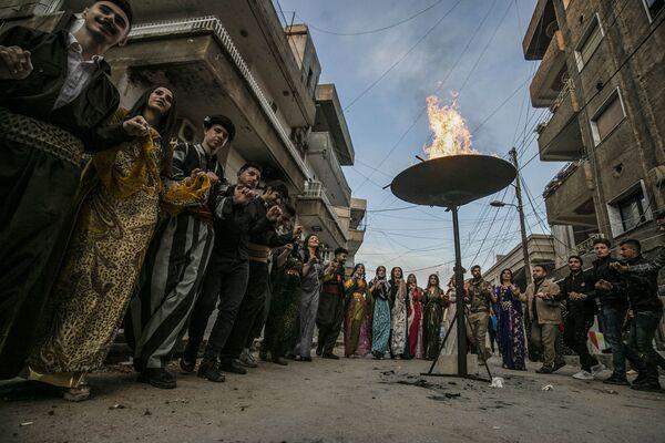 Uomini e donne curde nei propri costumi tradizionali celebrano il Nowruz con una danza intorno al fuoco nella città di Qamishly, in Siria - Sputnik Italia