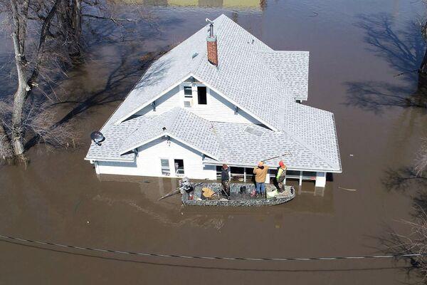 Lanni Bailey e una squadra di Muddy Paws Second Chance Rescue entrano in una casa allagata per tirare fuori diversi gatti durante l'alluvione del fiume Missouri vicino a Glenwood, Iowa, Stati Uniti il 18 marzo 2019. - Sputnik Italia