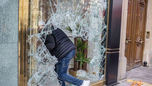 Parigi, proteste di piazza: un manifestante entra dentro un negozio dopo aver infranto la vetrina - Sputnik Italia