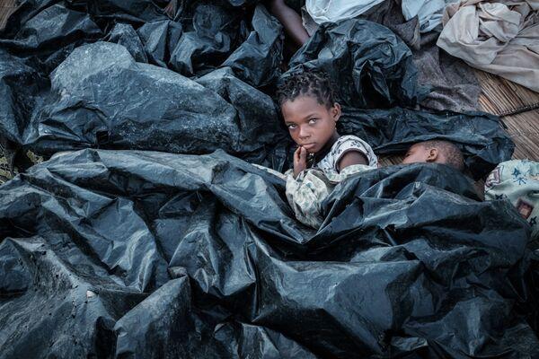 Enia Joaquin Luis, di 11 anni, con sua sorella Luisa, di 6 anni , si nascondono sotto le lastre di plastica per proteggersi dopo il ciclone che ha colpito il Mozambico. - Sputnik Italia