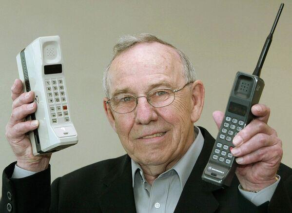 Anno 2003, l'ex capo del reparto Designe della Motorola, Rudy Krolopp, posa con in mano i primi due telefoni cellulari prodotti dalla sua azienda: il DynaTAC 8000X e l'International 3200 - Sputnik Italia